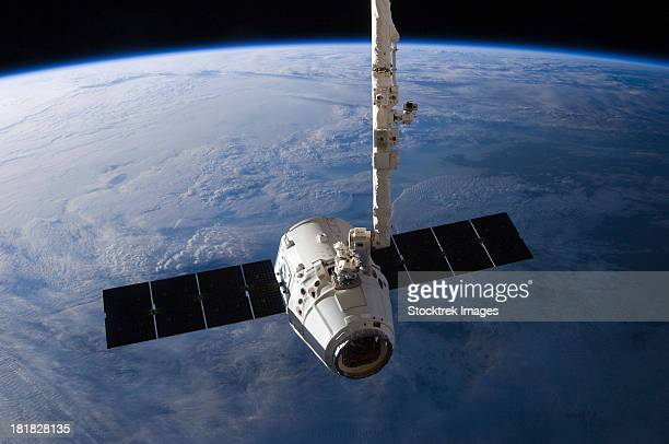 the spacex dragon cargo craft prior to being released from the canadarm2. - space station stock photos and pictures