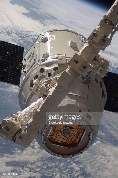 the spacex dragon commercial cargo craft during grappling operations with canadarm2. - orbiting stock-fotos und bilder