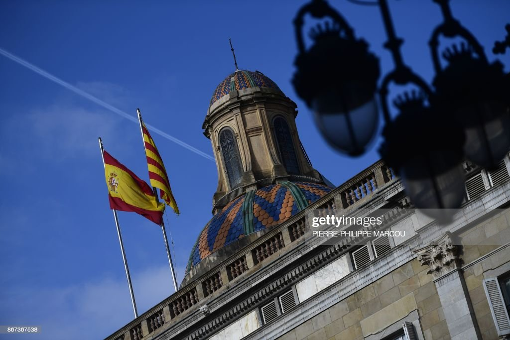 The Spanish (L) and Catalan Senyera flags flutter over Catalonia's Generalitat Palace in Barcelona on October 28, 2017, a day after direct control was imposed on the region over a bid to break away from Spain. Spain moved to assert direct rule over Catalonia, replacing its executive and top functionaries to quash an independence drive that has plunged the country into crisis and unnerved secession-wary Europe. /