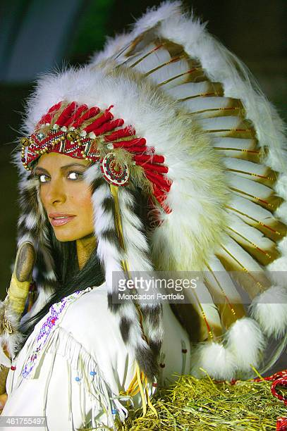 The Spanish showgirl Natalia Estrada posing with an Indian headdress in the stables of MHR in Cassano d'Adda Italy May 4th 2004