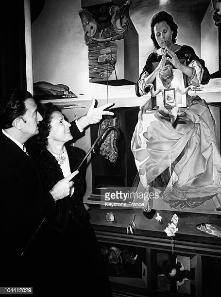 The Spanish Surrealist painter Salvador DALI and his wife - who often posed as his model - standing in front of his painting MADONNA OF PORT LLIGAT...