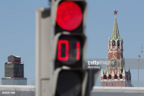 The Spasskaya tower of the Kremlin complex stands beyond a red traffic light during presidential elections in Moscow Russia on Sunday March 18 2018...