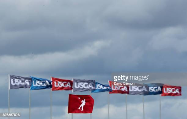 The special commemorative pin flag in memory of Arnold Palmer on the 18th green flutters in the wind during the final round of the 117th US Open...