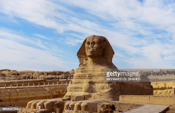 The Sphynx is seen in the foreground as tourists visit the pyramids on the Giza Plateau on the southern outskirts of the Egyptian capital Cairo on...
