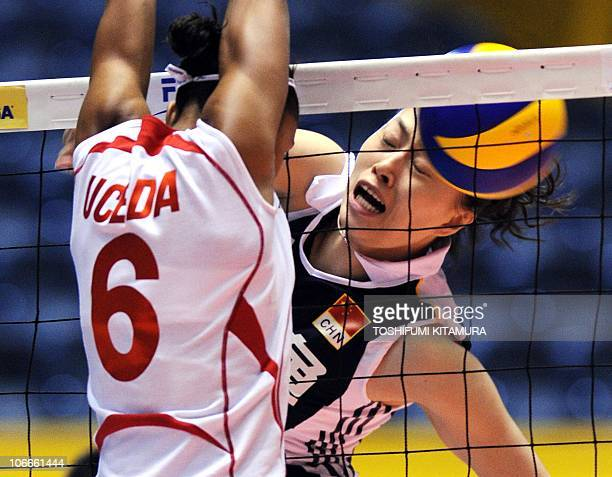 The spike by China's Ma Yunwen is blocked by Peru's Jessenia Uceda during their Pool E second round match at the FIVB 2010 Women's Volleyball World...