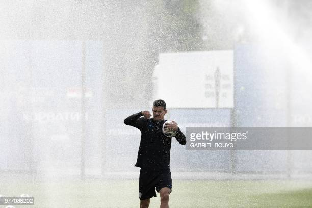 The spinklers go off as Croatia's defender Dejan Lovren attends a training session on June 17 2018 in Saint Petersburg during the Russia 2018 World...