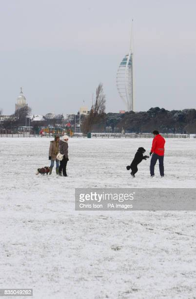 The Spinnaker Tower stands over dog walkers out on Southsea Common in Portsmouth as heavy snowfall hits the UK