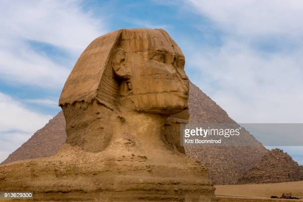 the spinx, an important landmark, sitting in front of pyramid of giza, egypt - egyptian culture stock photos and pictures
