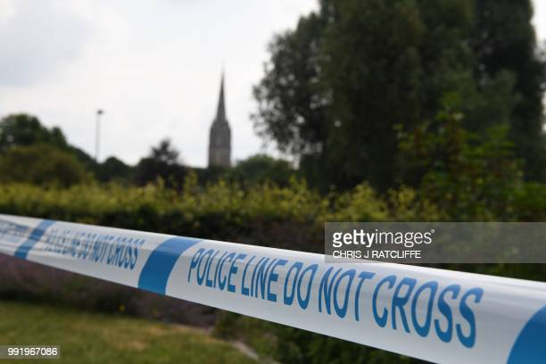 The spire of Salisbury Cathedral is seen behind police tape making a cordon around Queen Elizabeth Gardens in Salisbury southern England on July 5...