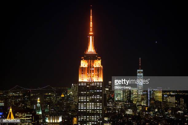 The spires of the Empire State Building center and One World Trade Center right stand lit in orange to support a bid for Amazoncom Inc's second...