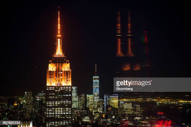 The spires of the Empire State Building left and One World Trade Center center stand lit in orange to support a bid for Amazoncom Inc's second...