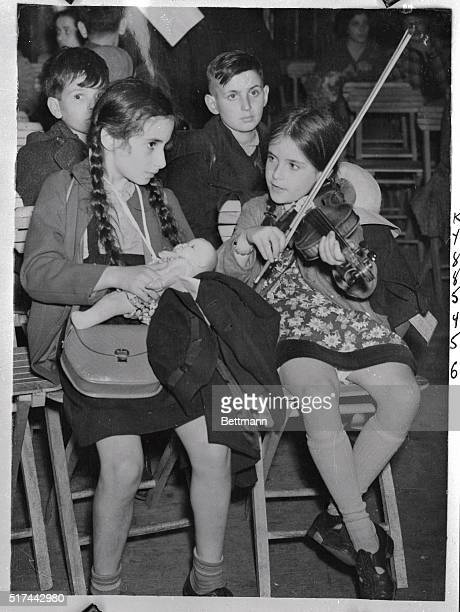 The spirits of these tiny refugees from Germany are buoyed by the tune one of their number plays on her violin as the 150 refugee children arrived at...