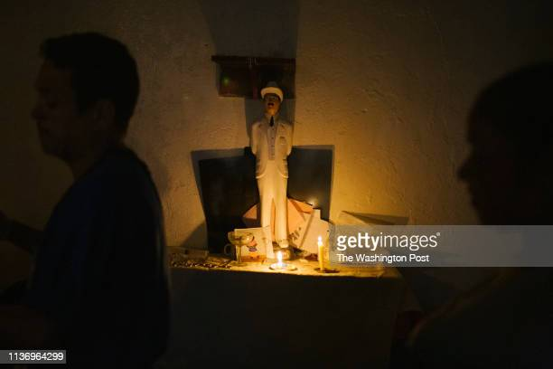 The spiritualist El Guayanes prays to Jose Gregorio Hernandez while treating a patient in the low income neighborhood of Petare in Caracas Venezuela...