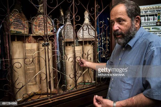 The spokesman for the Jewish community in Hebron Noam Arnon shows ancient Torah scrolls at the renovated 16th century Abraham Avinu Synagogue in the...
