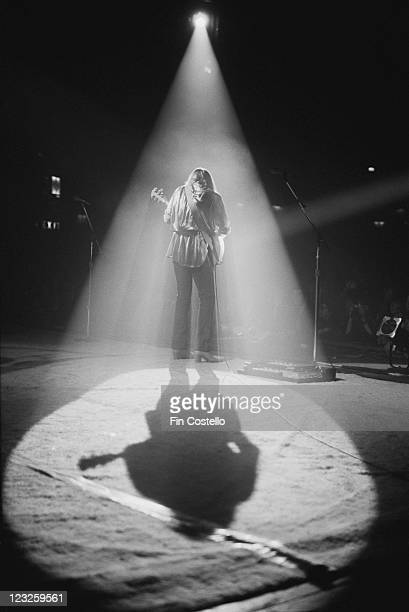 The spotlight lights Geddy Lee Canadian bassist and guitarist viewed from behind casting a shadow across the stage during a live concert performance...
