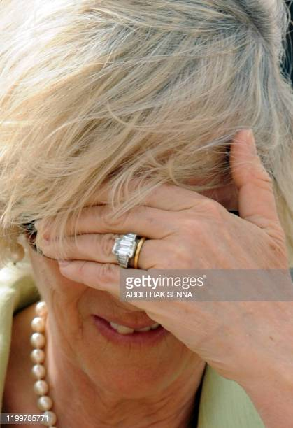 The spouse of Britain's Prince Charles Camilla shields her eyes from the wind as she visits on April 5 2011 the Oudayas Kasbah a fortified...