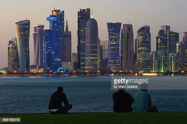 The sprawling skyline and waterfront at dusk in Doha, Qatar.