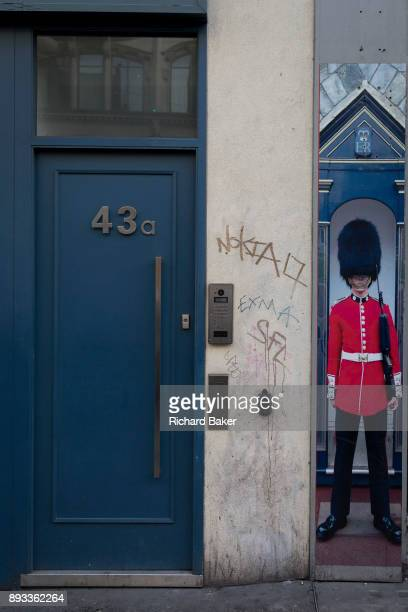 The squashed perspective of a grenadier guardsman standing as sentry next to a doorway and a closed down business a metaphor for Brexit on Oxford...