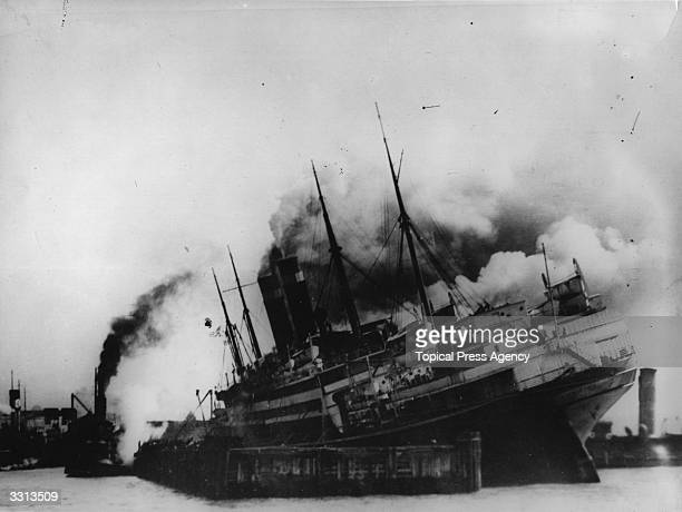 The SS America on fire while being refitted at New York harbour