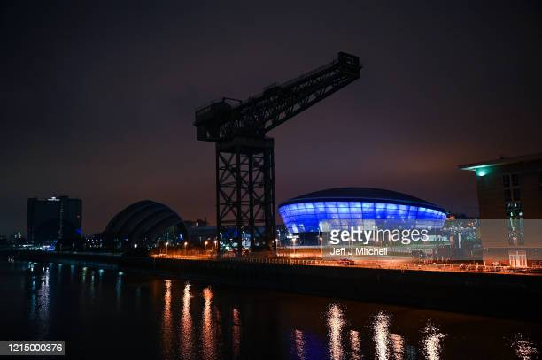 """The SSE Hydro is lit up blue for NHS staff for all their hard work during the outbreak on March 26, 2020 in Glasgow, United Kingdom. The """"Clap For..."""