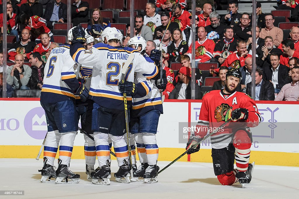 The St. Louis Blues celebrate after scoring and tying the game, as Brent Seabrook #7 of the Chicago Blackhawks kneels to the side, in the second period of the NHL game at the United Center on November 4, 2015 in Chicago, Illinois.