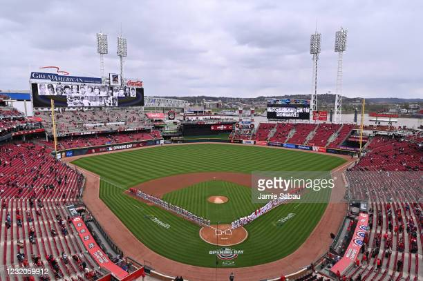 The St. Louis Cardinals and the Cincinnati Reds stand on the field to honor major league ballplayers who passed away in the last year before their...