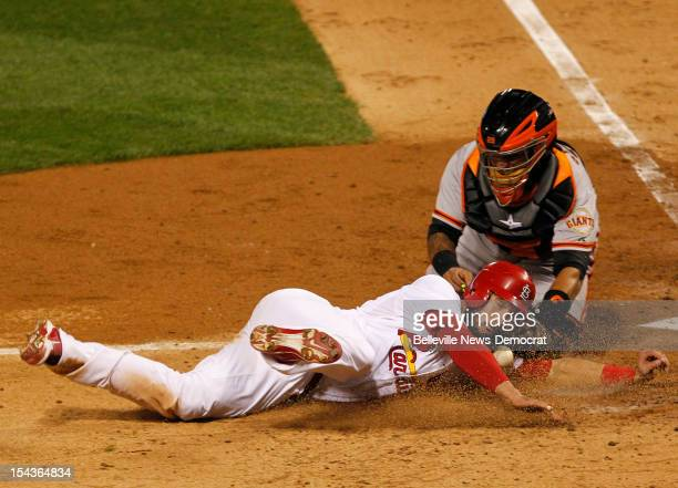 The St Louis Cardinals' Matt Carpenter slides safely into home to score as San Francisco Giants catcher Hector Sanchez reaches for the ball during...