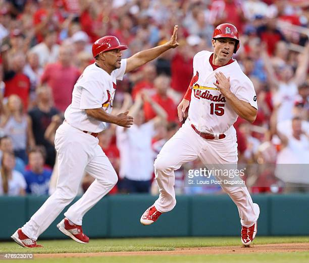 The St Louis Cardinals' Randal Grichuk runs past third base coach Jose Oquendo as he scores on a triple by Jon Jay in the second inning against the...