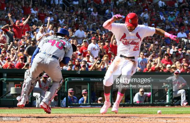 The St Louis Cardinals' Tommy Pham hops over a shovel pass from Chicago Cubs pitcher Jon Lester to catcher Willson Contreras left as he scores on a...