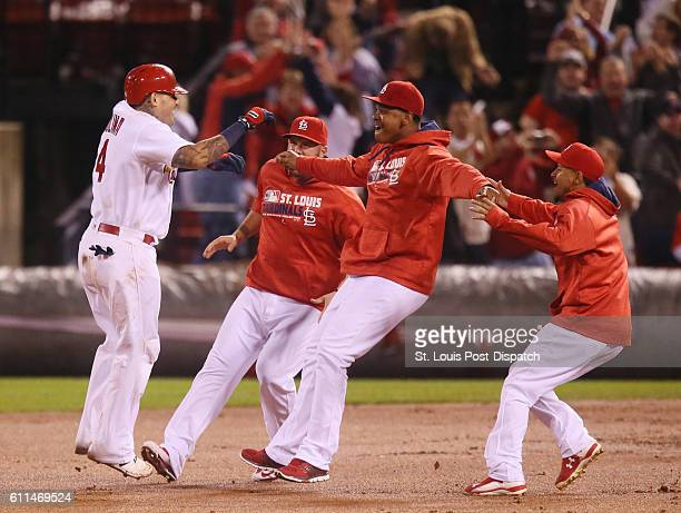 The St Louis Cardinals' Yadier Molina left is congratulated by teammates Matt Adams second from left Alex Reyes and Carlos Martinez right after he...