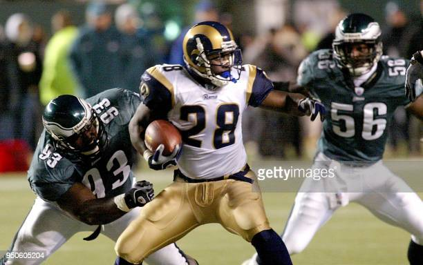 The St Louis Rams Marshall Faulk looks for running room as Levon Kirkland and Shawn Barber of the Philadelphia Eagles move into tackle him in the 4th...