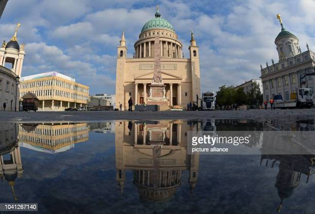 The St. Nicholas' Church mirrored by a puddle on the Old Market square in Potsdam, Germany, 24 September 2015. Photo: Ralf Hirschberger/dpa | usage...