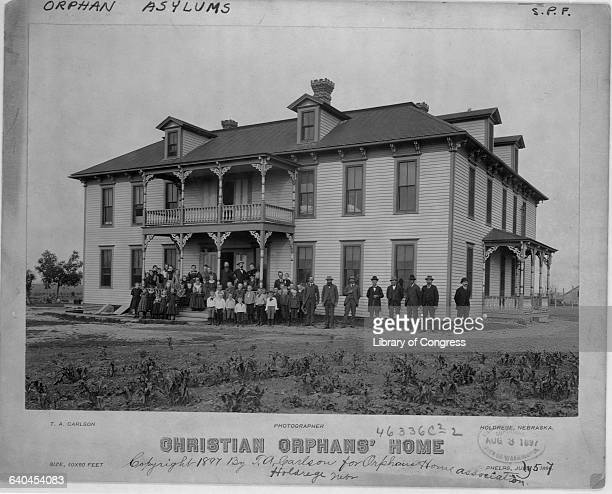 The staff and charges of the Christian Orphan's Home in Holdredge Nebraska stand outside of the orphanage building 1897 | Location Holdredge Nebraska...