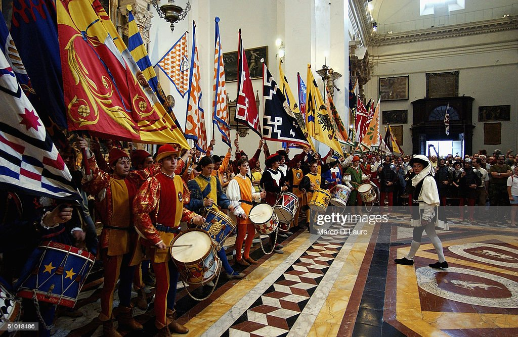 The standard bearer of the seventeen contrade, hold their flags inside the Basilica of Provenzano during the procession to pay their respect to the Madonna di Provenzano to who the Palio is entitled on July 1, 2004 in Siena, Italy. Before the Palio the banner is solemnly blessed in the Basilica of Provenzano. The city's 17 separate Contrade or neighbourhoods vie to compete in the prestigious Palio race, which takes place at the end of a week of festivities which encourage huge support and fierce competition between the participants.
