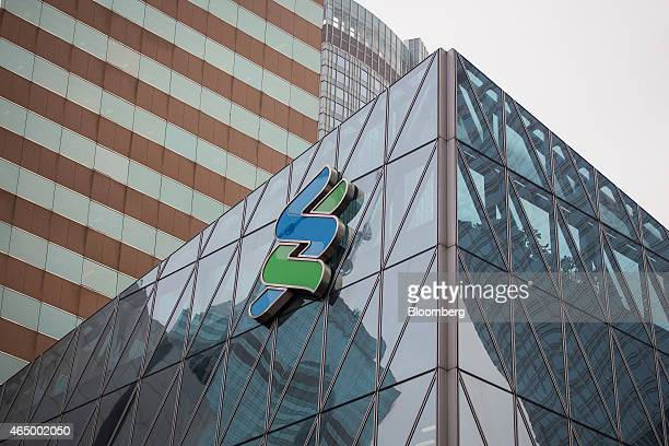 The Standard Chartered Plc logo is displayed atop the Standard Chartered Plc offices at the Forum building in the Central district of Hong Kong China...