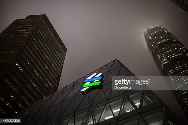 The Standard Chartered Plc logo is illuminated at night atop the company's offices at the Forum building in the Central district of Hong Kong China...