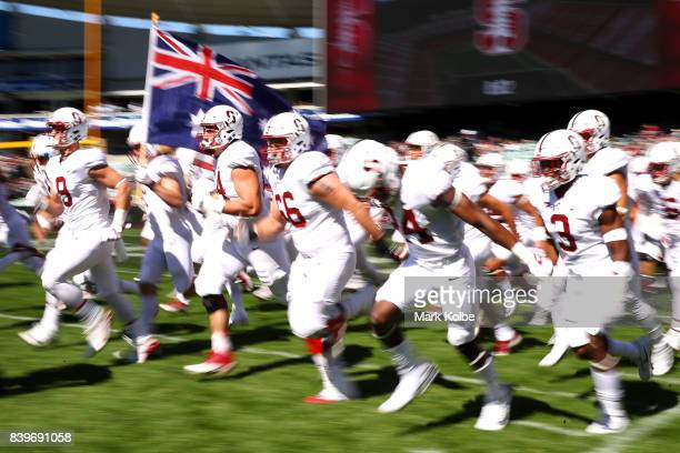 The Stanford team run out onto the field carrying an Australian flag for the start of the College Football Sydney Cup match between Stanford...