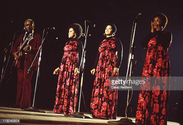 The Staple Singers US singing quartet lined up behind microphones during a live concert performance with Pervis Staples playing the guitar at the New...