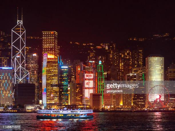 the star ferry crossing victoria harbour in hong kong at night - star ferry stock photos and pictures