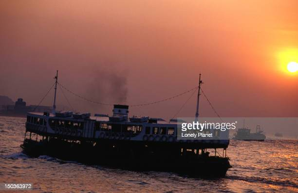 The Star Ferry makes its way across Hong Kong Harbour to Tsim Sha Tsui at sunset.