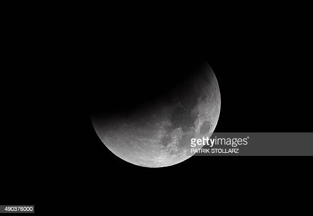 The start of total lunar eclipse to a blood moon is seen in the dark sky in Essen western Germany on September 28 2015 AFP PHOTO / PATRIK STOLLARZ