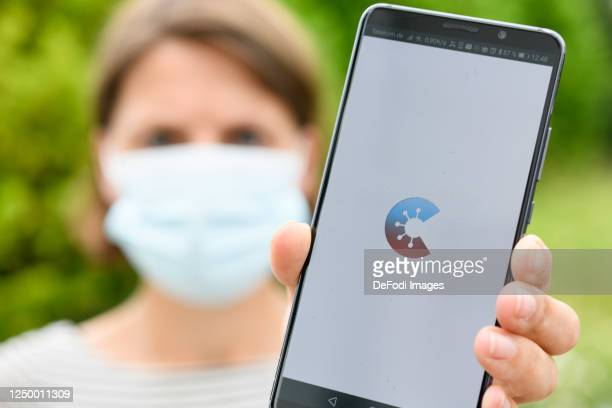 The start page of the Corona Warn app is seen on an Andriod smartphone The smartphone is held by a woman with a protective mask on June 16 2020 in...