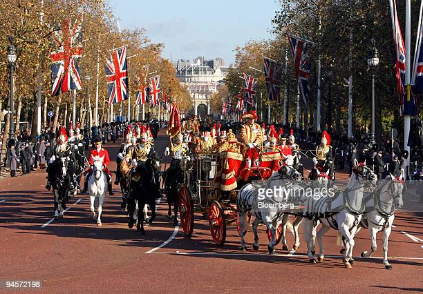 The state coach carrying Britain's Queen Elizabeth II travels down the Mall as it returns to Buckingham Palace following the State Opening of...