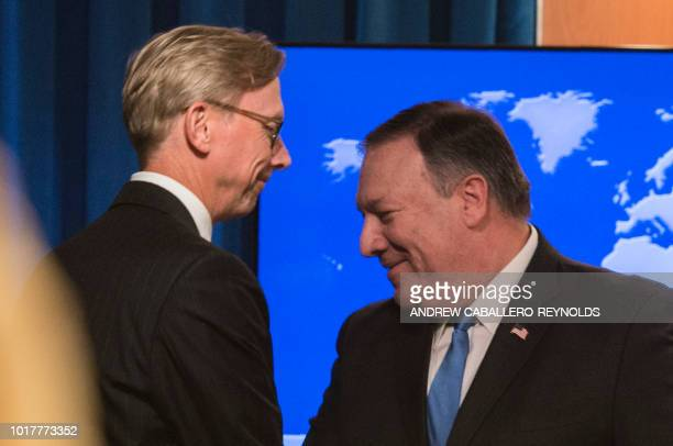 The State Department's director of policy planning and head of the Iran Action Group Brian Hook shakes hands with US Secretary of State Mike Pompeo...