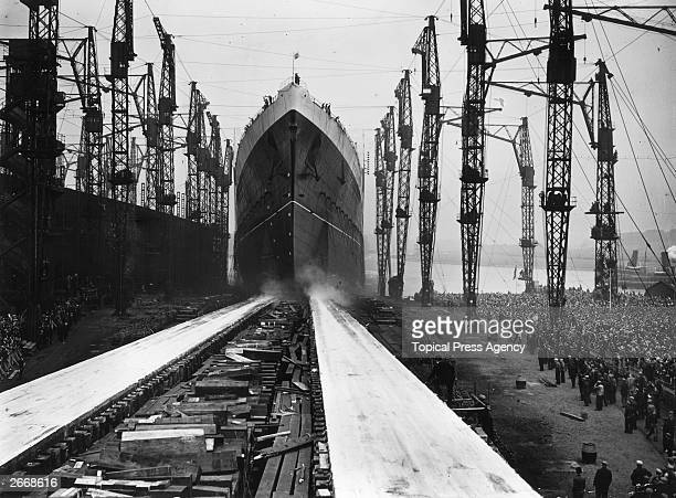 The stately Cunard liner Queen Elizabeth the largest liner ever built makes her way down the slips on the day of her launch from the John Brown Co...