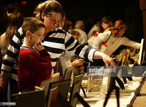 The Station Nightclub Remembrance Ceremony Kimberly Rich and her son Christopher look at pictures of the victims of The Station nightclub fire before...