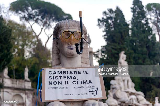 The Statue in Villa Borghese with masks and snorkels to send a message 'Act now to stay afloat' to the Italian government involved in the climate...