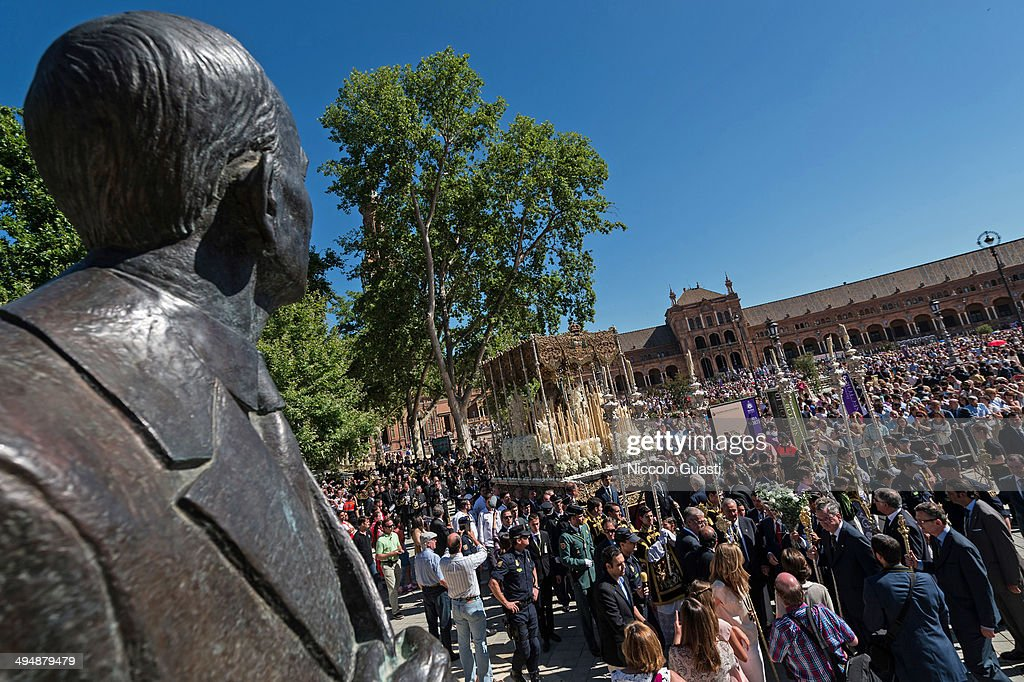 The statue of Anibal Gonzalez, the architect who projected the 'Plaza de Espana', facing the the figure of the Virgin during the 50th Anniversary of 'La Macarena' crowning in the 'Plaza de Espana' Square on May 31, 2014 in Seville, Spain. Seville locals and visitors from around the world come in the masses to observe the grande celebration of the Jubilee Year of La Macarena held to mark the 50th anniversary of the canonical coronation of the Virgin of La Macarena, a 17th century Roman Catholic wooden image of the Blessed Virgin Mary venerated in Seville and one of the city's most popular symbols.