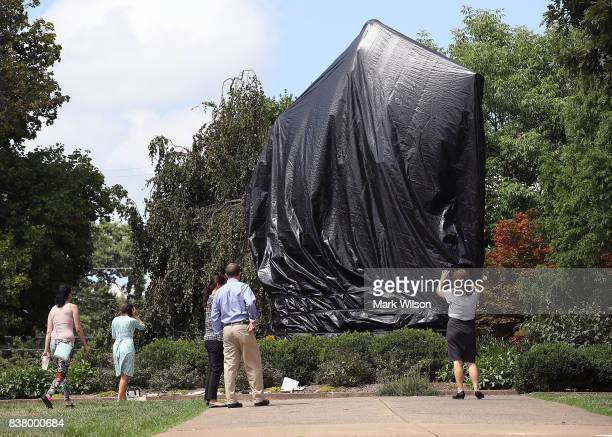 The statue of Confederate Gen Robert E Lee is covered with a black tarp as it stands in the center of Emancipation Park formerly Lee Park on August...