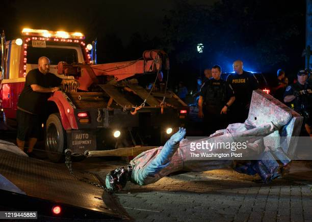 The statue of Confederate President Jefferson Davis is loaded onto a tow truck after it was pulled down off of it's pedestal on Monument Avenue in...